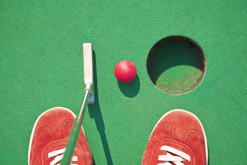 miniature golf hole with putter and red ball with red shoes