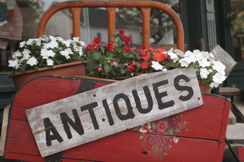 A flower box with potted flowers, with a wooden ANTIQUES sign attached.