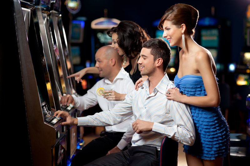 Friends enjoying playing the slot machine at the casino.